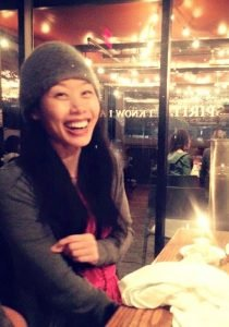 picture of Jennifer Huang red blouse, wood table, single candle on a cupcake, glass windows, cafe gratitude los angeles