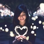 picture of Asian woman holding a light strands in heart shape at night