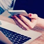 picture of woman's hand holding iphone near laptop